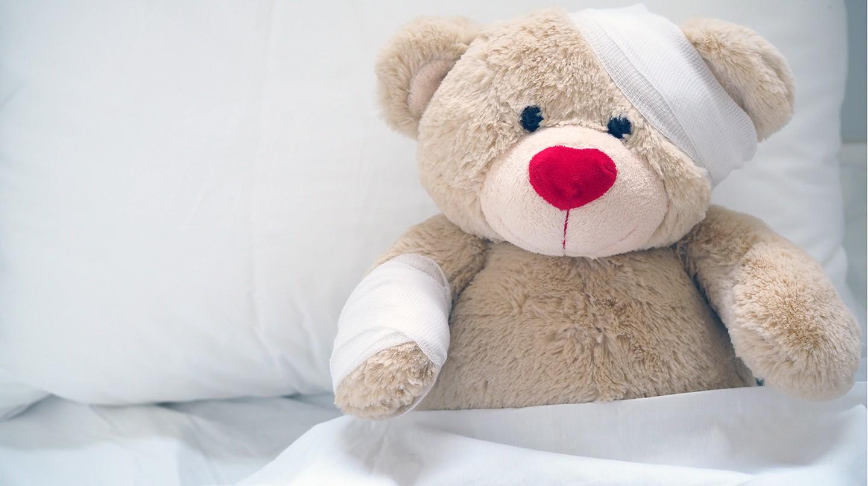 Erste Hilfe bei Kindern: Ein Teddybär ist im Bett und hat einen Verband um seinen Kopf.