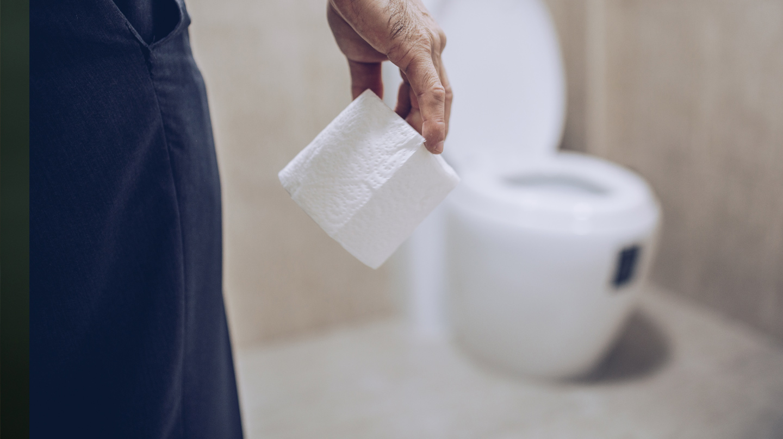 Hämorrhoiden: Eine Hand hält eine Rolle Toillettenpapier. Im Hintergrund eine Toilette mit aufgeklapptem Toilettendeckel..